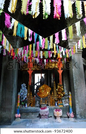 Buddhist shrine with colorful flags at banteay kdei temple, angkor, near siem reap, cambodia