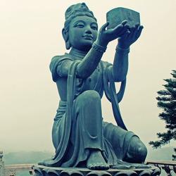 Buddhist Statue praising the Big Buddha (Tian Tan Buddha) on Lantau island (Hong Kong).Square image, instagram effect