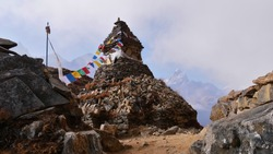 Buddhist stone monument with attached colorful prayer flags besides hiking trail near Phortse, Sagarmatha National Park, Himalayas, Nepal with majestic mountains vanishing in the rising clouds.