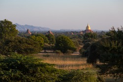 Buddhist temples over green jungle and mountains at the background, Bagan, Myanmar, Burma, south east Asia