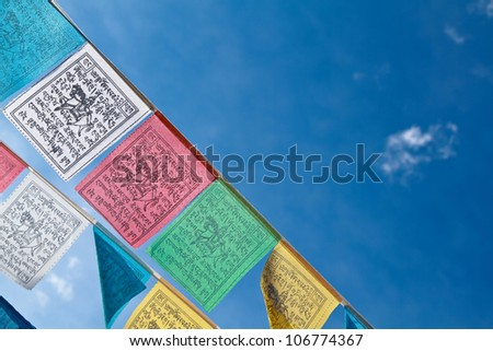 Buddhist tibetan prayer flags flying with blue sky