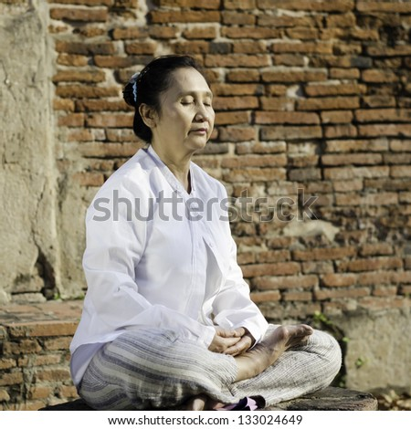 Buddhist woman meditating against ancient temple