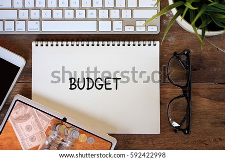 BUDGET business concept words on notebook with tablet pc, smartphone, glasses and keyboard on wooden table