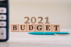 Budget 2021 concept. 2021 budget wooden cubes, calculator and a pen on wooden office table.