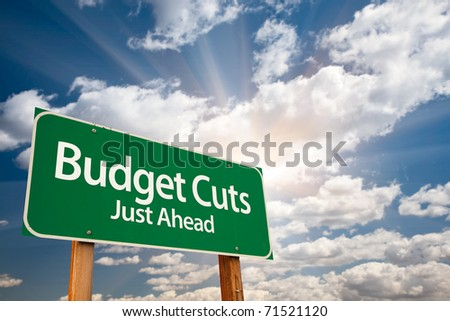 Budget Cuts Green Road Sign with Dramatic Clouds, Sun Rays and Sky. - stock photo