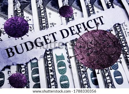 Budget Deficit news headline and Coronavirus on hundred dollar bills              Foto stock ©