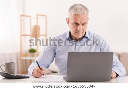 Budget Planning. Pensive Senior Man Using Laptop And Writing In Notebook Sitting At Desk At Home, Empty Space