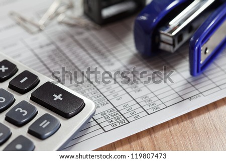 Budget spreadsheet with calculator, stapler, and paper clips on a wooden desk