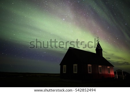 Budir Church on the Snaefellsnes Peninsula of Iceland at night with the Aurora borealis and stars behind it