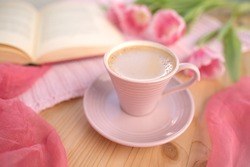 buds of spring flowers, pink tulips, a cup of cappuccino, book on a wooden table, concept of spring, women's lifestyle, morning mood