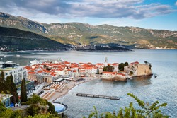 Budva old town houses architecture history Montenegro tourist landmark summer vacation travel destination. Daytime sky with clouds landscape panorama. Adriatic sea and mountains.