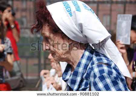 "BUENOS AIRES, ARGENTINA - NOV 17:An unidentified woman marches in Buenos Aires, with ""The Mothers of the Plaza de Mayo"" and wears a white shawl with the disappearance date of her child on Nov 17, 2011"