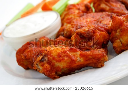 Buffalo chicken wings on plate with blue cheese sauce, carrots, and celery.