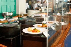 Buffet in Restaurant has Clear Acrylic Partition to protect droplet from customers to food cooking as new normal lifestyle. Cafe open again after releasing lockdown from Covid-19 coronavirus pandemic.