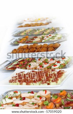 Buffet on a long table with appetizers or finger food