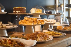 buffet table displays a variety or array of delicious baked goods and pastries from savoury to sweet at a coffee shop or cafe in chic urban environment for snack or lunch time consumption