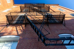 Bug eye view of vintage black metal construction fire escape ladder with makeshift balconies and access to egress windows attached on the side of an old  brick apartment.