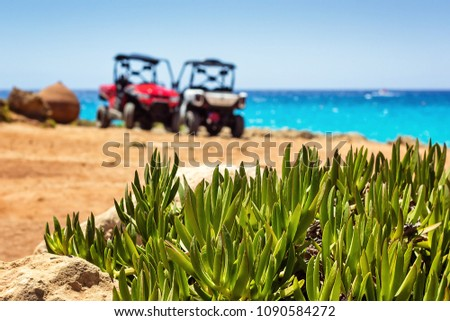 Buggy parked convertible car on the beach near the sea and clear blue sky with green plants. Off-road car is major tourists attraction and popular touristic transport for rent at Cyprus, Nissi beach.  #1090584272
