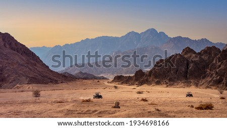 Buggy trip in a stone desert at sunset. Mountain landscape with off-road vehicles driving on a dust dirt road. Active leisure for tourists in Sharm el-Sheikh resorts, Egypt.