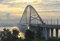 Bugrinskij bridge road at sunrise. The high arch of the cable-stayed bridge in the fog across the Ob river, powerful concrete pillars, Golden dawn, the Sun in the clouds, Smoking pipes on the horizon