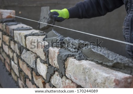 Build a brick wall, bricklaying spreading a bed joint. Bricklaying foundation walls, spread a mortar bed joint for building brick. Brick mason laying old brick.