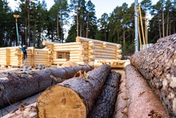Build a house from logs. Preparation of logs for the assembly of the structure. Assembly of a wooden log house at a construction base.