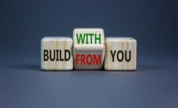 Build from or with you symbol. Turned the wooden cube and changed words 'build from you' to 'build with you'. Beautiful grey background, copy space. Business, build from or with you concept.