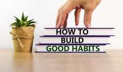 Build good habits symbol. Books with text 'how to build good habits' on beautiful wooden table. Male hand, house plant. White background. Business and build good habits concept. Copy space.