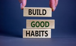 Build good habits symbol. Wooden blocks with words 'build good habits'. Male hand. Beautiful grey background, copy space. Business, psychological and build good habits concept.