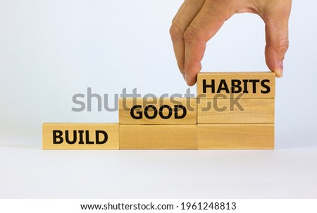 Build good habits symbol. Wooden blocks with words 'build good habits'. Male hand. Beautiful white background, copy space. Business, psychological and build good habits concept. Сток-фото ©