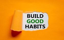 Build good habits symbol. Words 'Build good habits' appearing behind torn orange paper. Beautiful orange background. Business, psychology and build good habits concept, copy space.