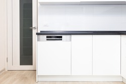 Build-in dishwasher in a white kitchen with black counter top.