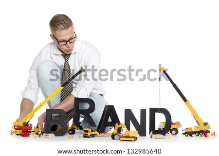 Build up a brand concept: Focused businessman building the word brand along with construction machines, isolated on white background.