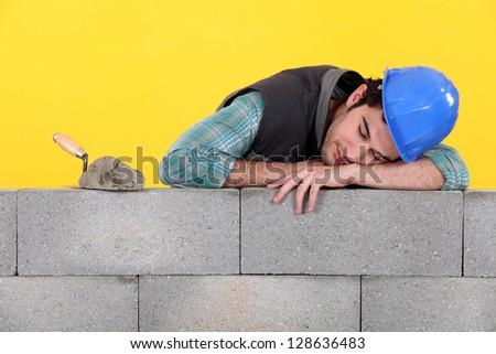 Builder asleep on a wall