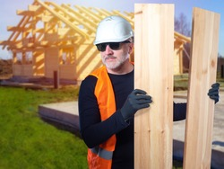 Builder at a construction site. Man on background of a house under construction. Builder holds wooden beams in his hands. Building a house of wood. Builder carries boards to construction site