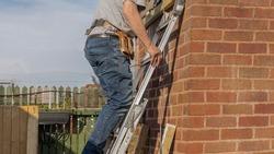 Builder climbing a ladder to work