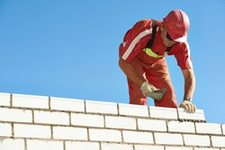 Builder construction mason worker bricklayer installing red brick with trowel putty knife outdoors