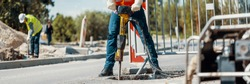 Builder drilling the road with a tool and his coworker at the city road work construction site in the blurry background