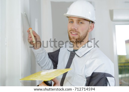 builder filling the holes on the wall #712714594
