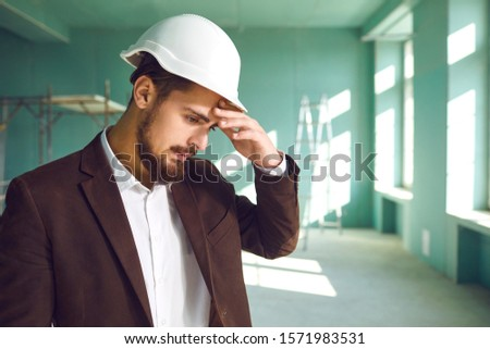 Builder foreman in a white helmet surprised in shock at a construction site indoors