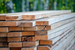 Builder in a protective helmet holds wooden planks. Concept - sale of lumber. Builder is considering wood planks. Concept - wood processing business. wood timber stack of wooden planks.
