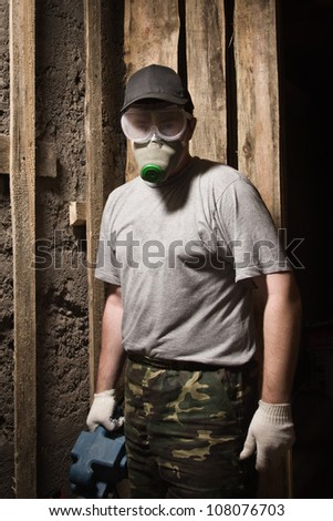 Builder in a respirator and goggles with sander