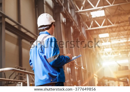 Shutterstock builder in hard hat looking at an industrial interior. Metal smelting plant