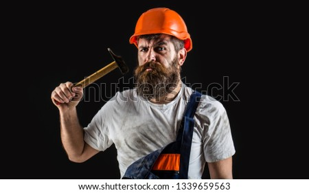 Builder in helmet, hammer, handyman, builders in hardhat. Bearded man worker with beard, building helmet, hard hat. Hammer hammering.