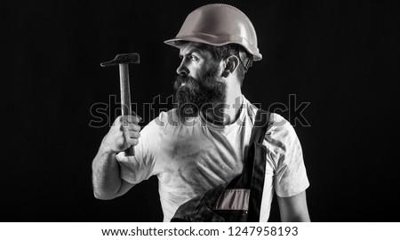 Builder in helmet, hammer, handyman, builders in hardhat. Handyman services. Hammer hammering. industry, technology, builder man, concept. Bearded man worker with beard, building helmet, hard hat.