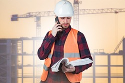 Builder is calls talking on phone. Tower crane is behind him. Builder calls customer. Builder in working uniform holds papers. Construction of high-rise buildings in background. Calls architect.