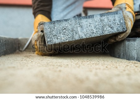 Builder laying a paving brick placing it on the sand foundation with gloved hands.
