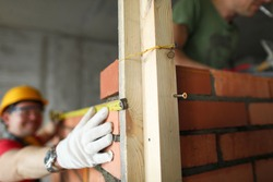 Builder makes measurements with a tape measure on brickwork. In the foreground a wooden structure for a brick wall