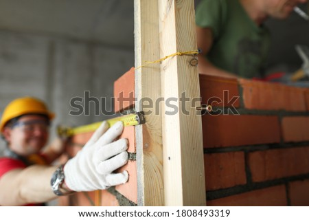 Builder makes measurements with a tape measure on brickwork. In the foreground a wooden structure for a brick wall Foto stock ©