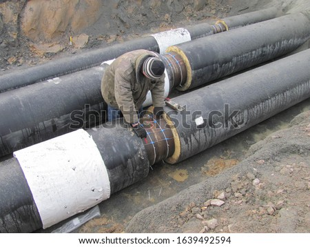 Builder man and Industrial large diameter black metal pipes. Real process of construction on a building site, laying pipes, debris, pipeline, conduit, pipe, piping, tubing, duct